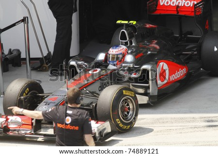 SEPANG, MALAYSIA - APRIL 8: Jenson Button of Vodafone McLaren Mercedes exits garage during PETRONAS Malaysian Grand Prix on April 8, 2011 in Sepang, Malaysia. The race will be held on April 10, 2011. - stock photo