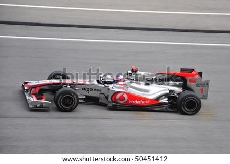 SEPANG, MALAYSIA - APRIL 4: Jenson Button of Vodafone McLaren Mercedes speeding during Petronas Malaysian Grand Prix at Sepang F1 circuit April 4, 2010 in Sepang, Malaysia - stock photo
