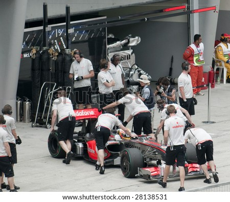 SEPANG, MALAYSIA - APRIL 3: Mechanics push Lewis Hamilton's car of Vodafone McLaren Mercedes during practice session at Malaysian F1 Grand Prix April 3, 2009 at Sepang International Circuit in Sepang. - stock photo