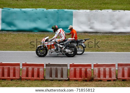 SEPANG, MALAYSIA - FEBRUARY 23: Marco Simoncelli gets help to return to the pits after a crash during the 2011 MotoGP winter tests at the Sepang International Circuit. February 23, 2011 in Malaysia. - stock photo