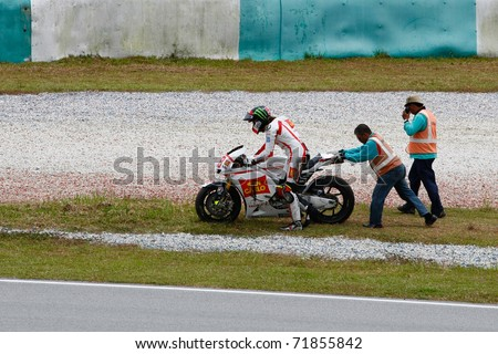 SEPANG, MALAYSIA - FEBRUARY 23: Marco Simoncelli of San Carlo Honda Gresini gets up after a crash at the 2011 MotoGP winter tests at the Sepang International Circuit. February 23, 2011 in Malaysia. - stock photo