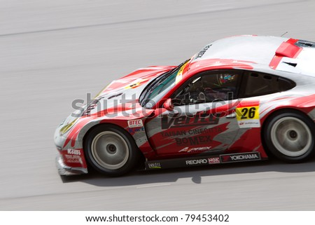 SEPANG, MALAYSIA - JUNE 18: Close up of Team Taisan in their Porsche 911 going down the high speed main straight during qualifying at Super GT International series June 18, 2011 in Sepang, Malaysia - stock photo