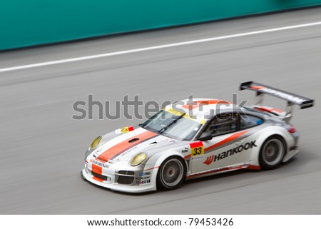 SEPANG, MALAYSIA - JUNE 18: Team Hankook in their Porsche 911 going down the high speed main straight during qualifying at Super GT International series June 18, 2011 in Sepang, Malaysia - stock photo