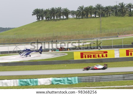 SEPANG, MALAYSIA - MARCH 23: A McLaren F1 car drives past the Pirelli Board to the pitlane during Friday practice at Petronas Formula 1 Grand Prix March 23, 2012 in Sepang, Malaysia - stock photo