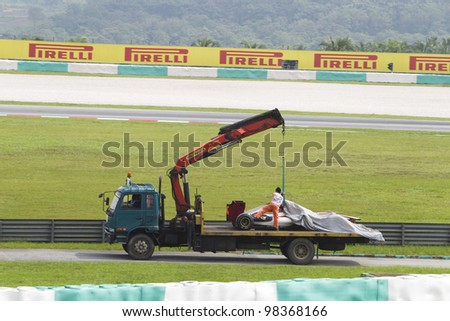 SEPANG, MALAYSIA - MARCH 23: A Team HRT F1 car towed back to the pits after an accident during Friday practice at Petronas Formula 1 Grand Prix March 23, 2012 in Sepang, Malaysia - stock photo