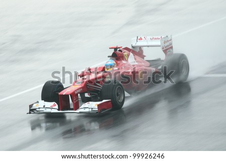 SEPANG,MALAYSIA-MARCH 25: Fernando Alonso of Scuderia Ferrari team in action in rain-hit Formula One PETRONAS Malaysian Grand Prix at Sepang F1 Circuit on March 25,2012 in Sepang, Malaysia.Alonso won. - stock photo
