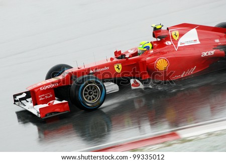 SEPANG, MALAYSIA - MARCH 25: Ferrari Team driver Felipe Massa action on wet track during race day of Petronas F1 Malaysian Grand Prix at Sepang Circuit on March 25, 2012 in Sepang, Malaysia - stock photo