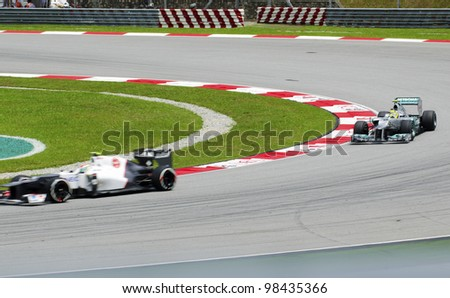 SEPANG, MALAYSIA-MARCH 23 : Formula One drivers speeding at corner in motion blur races during the first practice session on March 23, 2012 in Sepang International Circuit in Sepang, Malaysia.