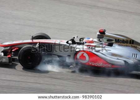 SEPANG, MALAYSIA - MARCH 23: Jenson Button of Vodafone McLaren Mercedes brakes hard during Petronas Malaysian Grand Prix practice session at Sepang F1 circuit on March 23, 2012 in Sepang, Malaysia. - stock photo