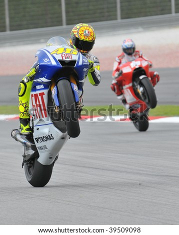 SEPANG, MALAYSIA - OCT 23 : Italian Valentino Rossi (L) of Fiat Yamaha Team does a wheelie at Shell Advance Malaysian Motorcycle Grand Prix October 23, 2009 in Sepang. Nicky Hayden in the background.
