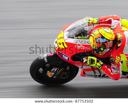 SEPANG, MALAYSIA - OCTOBER 21: MotoGP rider Valentino Rossi tests his bike during the free practice session at the Shell Advance Malaysian Motorcycle GP 2011 on October 21, 2011 in Sepang, Malaysia. - stock photo