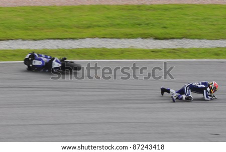 SEPANG, MALAYSIA - OCTOBER 21: Yamaha rider Katsuyuki Nakasuga  falls at turn 15 during free practice at the Shell Advance Malaysian Motorcycle GP 2011 on October 21, 2011 at Sepang, Malaysia.