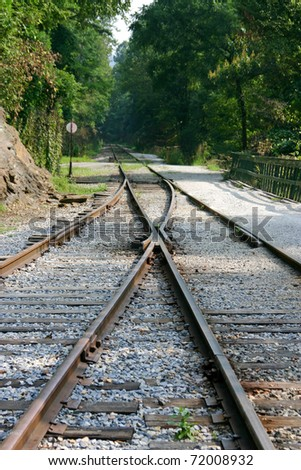 Separate train tracks merging and diverging going off into the unknown - stock photo