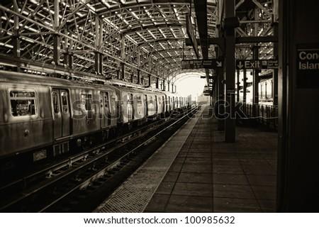 Sepia image of train and platform at the Coney Island subway station - stock photo