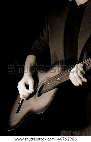 sepia man and guitar at black background - stock photo