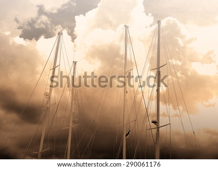 Sepia masts of Sail Yacht on cloudy burn sky,created image more noise - stock photo
