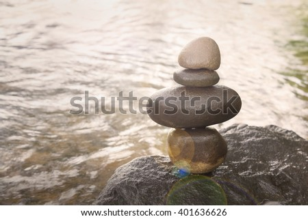 Sepia nature picture of superimposed waterfall pebble rock arranged on big stone at waterfall background with copy space