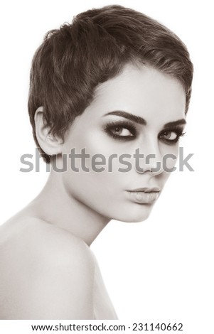 Sepia portrait of young beautiful woman with stylish haircut and smokey eyes - stock photo