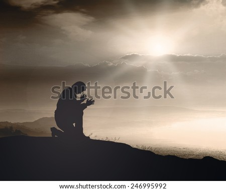 Sepia tone. The lonely man. People kneeling and praying over sunset background. - stock photo