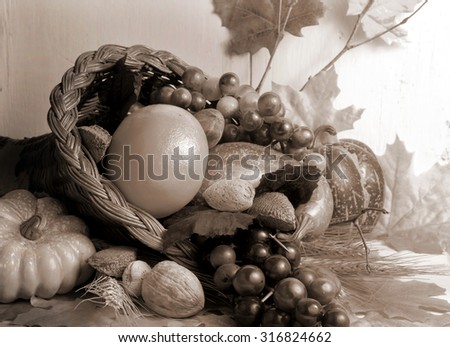Sepia toned close up image of fall cornucopia containing fruits and vegetables and nuts with autumn leaves scattered around with rustic wood background.  Horizontal composition. Good for fall harvest. - stock photo