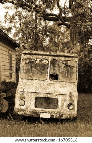 Sepia toned courier or maybe ice cream truck abandoned and covered in moss and lichens