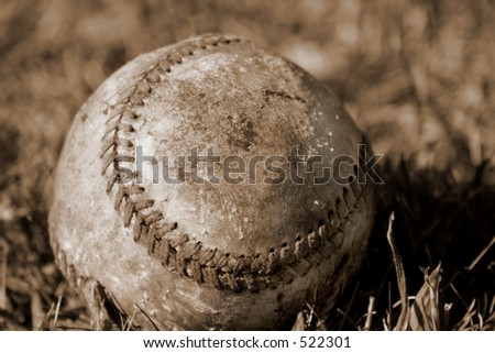 Sepia-toned distressed baseball in the grass - stock photo