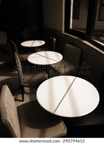 Sepia toned image of the interiors of a cafe. There are three white tables and six chairs by the window. Sun lights come in from the window and cast shadows on the desk and chairs.  - stock photo