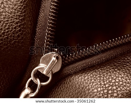 sepia toned leather swatch with zipper fragment - stock photo