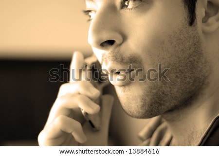 Sepia toned portrait of a young man on his cell phone - he looks surprised from what he has just heard. - stock photo