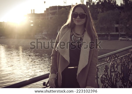Sepia toned retro portrait of a beautiful girl in sunglasses backlit against water, instagram style. - stock photo
