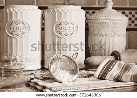 Sepia toned still-life of flour spilling from vintage sieve with antique rolling pin and old-fashioned canisters on kitchen counter.