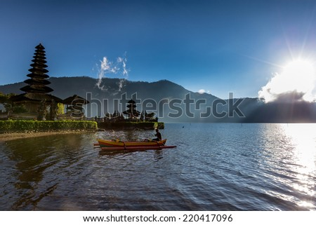 SEPTEMBER 17, 2014 - BALI, INDONESIA: A fisherman rowing a traditional Balinese out-rigger travels across the volcano crater lake of Lake Bratan, Bali Island, Indonesia. - stock photo