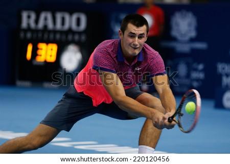 SEPTEMBER 23, 2014 - KUALA LUMPUR, MALAYSIA: Bernard Tomic of Australia makes a backhand return in his first round match at the Malaysian Open Tennis 2014 event. This is an ATP sanctioned tournament. - stock photo