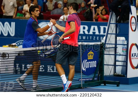SEPTEMBER 23, 2014 - KUALA LUMPUR, MALAYSIA: Bernard Tomic (red) congratulates Pierre-Hugues Herbert for his first round win at the Malaysian Open Tennis 2014. This is an ATP sanctioned tournament. - stock photo