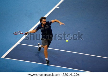 SEPTEMBER 25, 2014 - KUALA LUMPUR, MALAYSIA: Ernests Gulbis of Latvia chases to make a forehand return in his match at the Malaysian Open Tennis 2014. This is an ATP sanctioned tournament. - stock photo