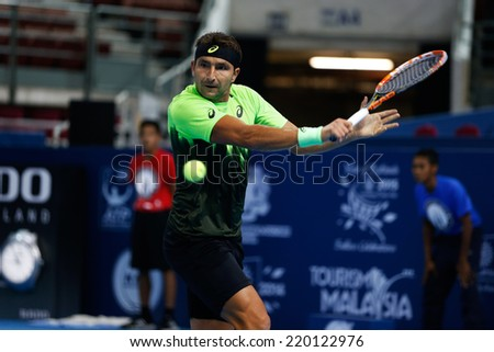 SEPTEMBER 23, 2014 - KUALA LUMPUR, MALAYSIA: Marinko Matosevic of Australia makes a backhand return in his first round match at the Malaysian Open Tennis 2014. This is an ATP sanctioned tournament. - stock photo