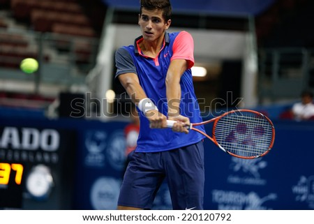 SEPTEMBER 23, 2014 - KUALA LUMPUR, MALAYSIA: Pierre-Hugues Herbert of France makes a backhand return in his first round match at the Malaysian Open Tennis 2014. This is an ATP sanctioned tournament. - stock photo