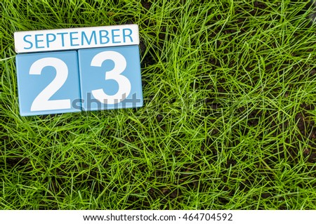 September 23rd. Day 23 of month, wooden color calendar on green grass lawn background. Autumn time. Empty space for text