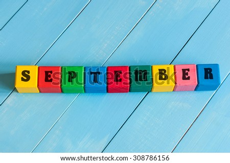 September sign on color wooden cubes with light blue wood background. - stock photo