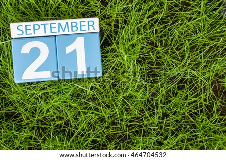 September 21st. Day 21 of month, wooden color calendar on green grass lawn background. Autumn time. Empty space for text