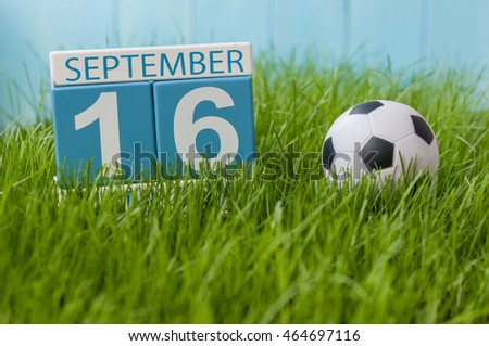 September 16th. Day 16 of month, wooden color calendar on green grass lawn background. Autumn time. Empty space for text