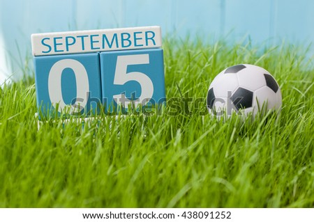 September 5th. Image of september 5 wooden color calendar on green grass lawn background. Autumn day. Empty space for text - stock photo