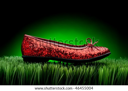 Sequined red slipper on green grass against a fading green background - stock photo