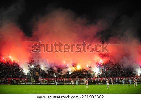 SERBIA, BELGRADE - SEPTEMBER 20, 2014: Soccer or football fans celebrating goal using pyrotechnics during Serbian championship soccer game between Red Star Belgrade and Novi Pazar Football club - stock photo
