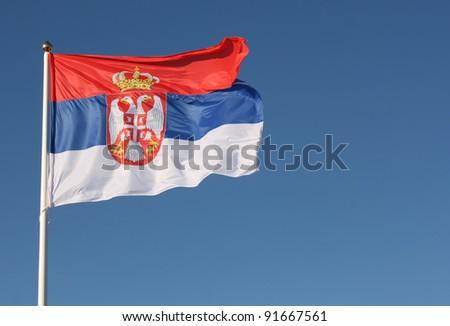Serbian flag waving on wind against clear blue sky - stock photo