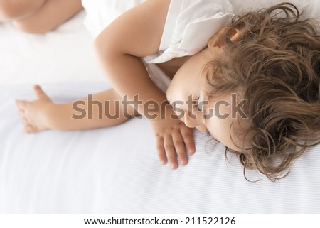 Serene and cute baby sleeping on a pillow in the bed - stock photo
