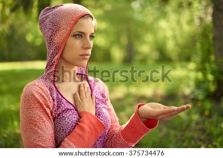 Serene and peaceful woman practicing mindful awareness mindfulness by meditating in nature at sunset - stock photo
