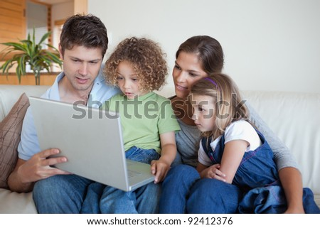 Serene family using a notebook in their living room - stock photo