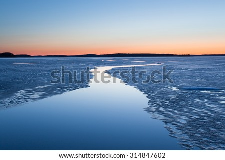 Serene frozen lake scape at twilight in finland - stock photo