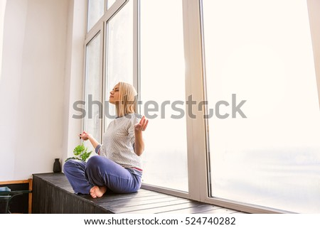 Serene girl doing meditation near window